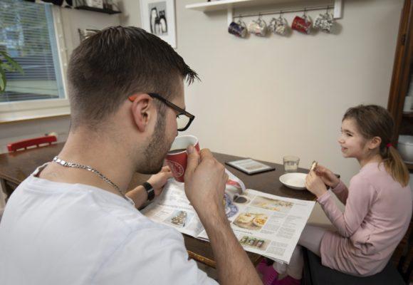 Isä ja lapsi lukevat sanomalehteä keittiön pöydän ääressä aamulla.