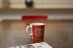 Kahvikuppi ja sanomalehti pöydällä.
